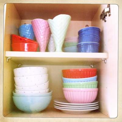 This cupboard hides a colourful medley of different bowls and plates.