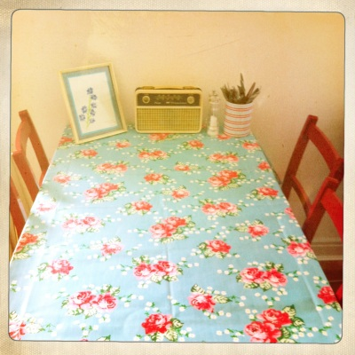 This gorgeous floral tablecloth works brilliantly with the pillar-box red painted chairs.