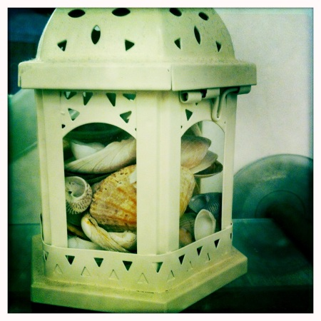 This old tea light holder is filled with shells to recreate a coastal feel.