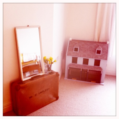 This vintage dolls' house and old-fashioned suitcase create a lovely, nostalgic feel in the guest room.