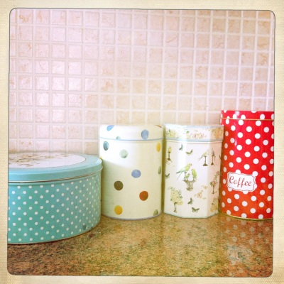 A colourful collection of different tins brighten up the kitchen bench.