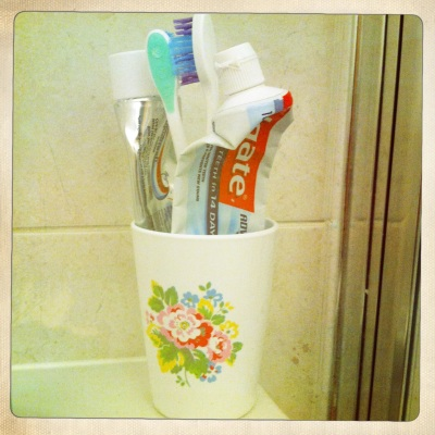 A pretty plastic beaker doubles up as a toothbrush holder.