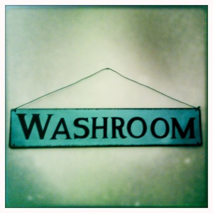 This blue metal vintage-style sign ties in with the bathroom's coastal theme.